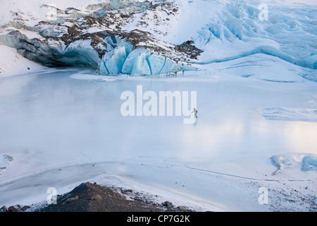 Woman ice skating in front of Saddlebag Glacier, Chugach Mountains near Cordova, Southcentral Alaska, Winter - Stock Photo