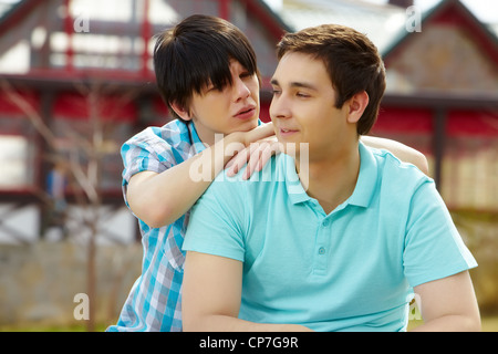 Young homosexuals enjoying each other's company in townhouse area - Stock Photo