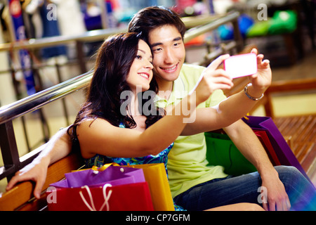 Smiling shoppers taking a picture of themselves - Stock Photo