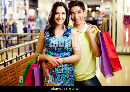 Portrait of two shoppers doing purchases in the mall - Stock Photo