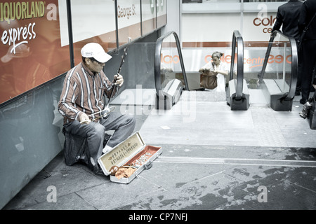 An old street performer playing chinese musical instrument in the city - Stock Photo