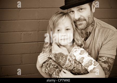 Father holds his five year old daughter and looks at camera. - Stock Photo
