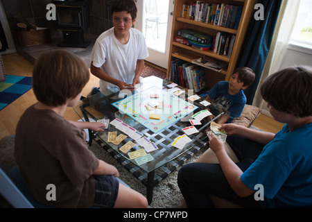 Four boys sitting on the floor playing Monopoly board game. - Stock Photo