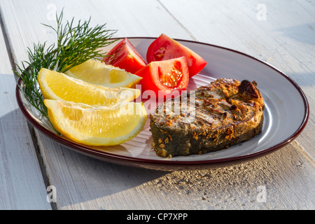 Fried fish served with tomatoes and lemon - Stock Photo