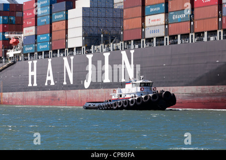 Hanjin shipping container ship, flagged by a tugboat, entering port of Oakland - California USA - Stock Photo