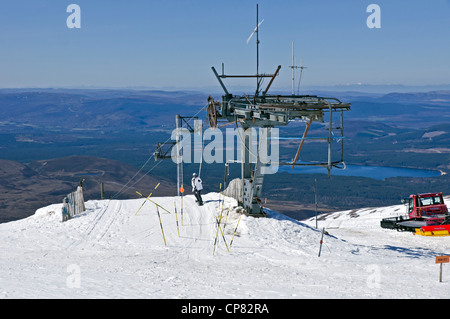 Snowboarder arriving at the top station on the Cairngorm Mountain ski resort  in Speyside Scotland on a May day - Stock Photo