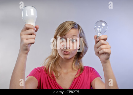 Young woman holding an energy-saving lamp and a conventional light bulb in his hands. She looks skeptical.