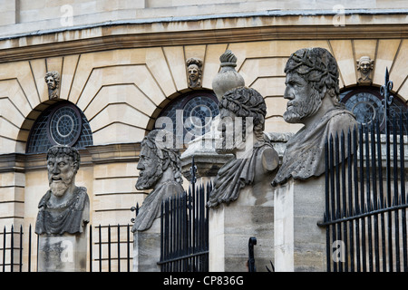 Carved stone busts on plinths outside Sheldonian theatre, Oxford, Oxfordshire, England - Stock Photo