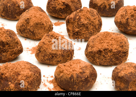 Bunch of chocolate truffles with cocoa powder on a white surface