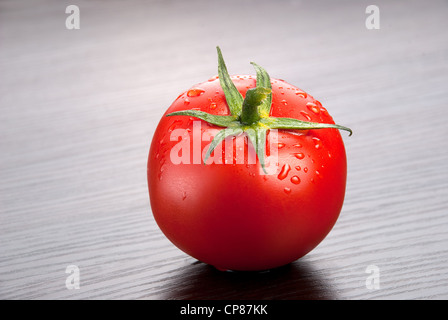 one fresh tomato with drops of water on the wooden background - Stock Photo