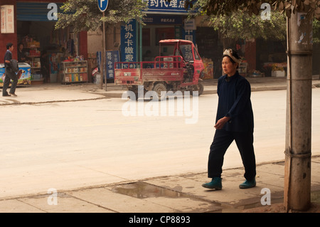 Dong woman walking on the pavement, China - Stock Photo