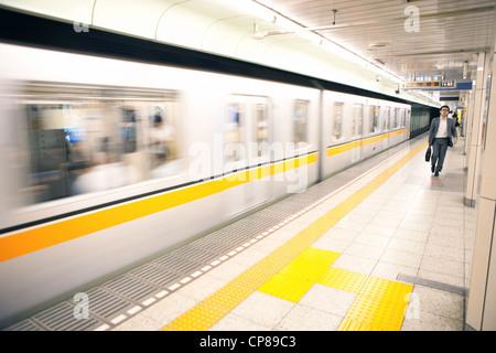 Man walking on platform of a Tokyo subway station, Japan. - Stock Photo