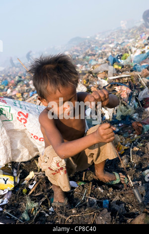 A young boy child laborer is using a gaff to collect soft clear plastic at The Stung Meanchey Landfill in Phnom - Stock Photo