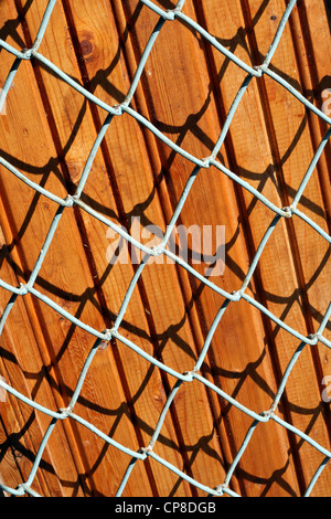 Texture background of the pine boards and metal lattice on sunlight. - Stock Photo