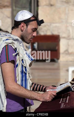 Young Jewish man reading torah wearing kippah, praying shawl & tefillin at Wailing wall, Jerusalem. Israel - Stock Photo