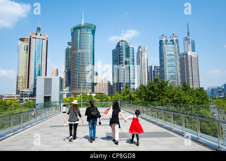 People walking on overhead walkway with skyline of skyscrapers in Lujiazui district of Pudong in Shanghai China - Stock Photo