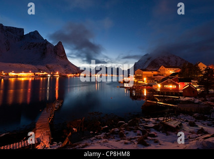 A night view of Reine village and Reinefjord, with the mountains of Navaren and Olstind in the background - Stock Photo