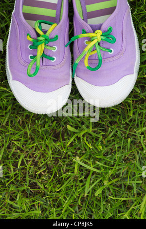 Colourful childs plimsolls on a grass lawn - Stock Photo
