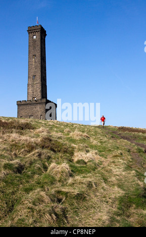 Walker passing Peel Tower, Holcombe Hill, above Ramsbottom, West Pennines, Greater Manchester / Lancashire, England,UK - Stock Photo