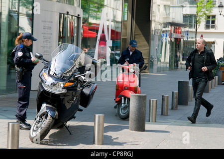 Traffic enforcement officer issuing a ticket for illegally parked Vespas in Paris, France - Stock Photo
