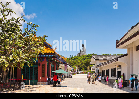 Visitors in the main street of Ngong Ping on Lantau Island, Hong Kong, dominated by the Tian Tan Buddha statue. - Stock Photo