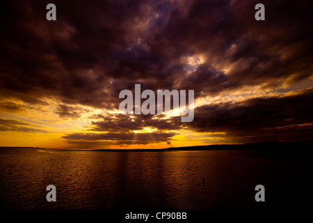 The sun setting across the Loughor Estuary, Swansea. - Stock Photo
