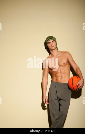 Portrait of Healthy and good looking young caucasian man in long pants holding a basketball. - Stock Photo