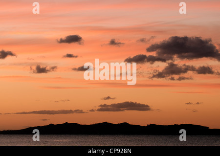 Colorful clouds during sunrise and sunset above a island. - Stock Photo