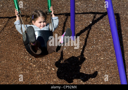 A little girl plays on a swing in a playground. - Stock Photo