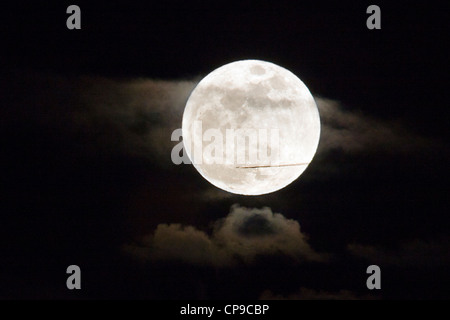 Commercial jet flies in front of a perigree full moon, or supermoon, rising over Salida, Colorado, USA - Stock Photo