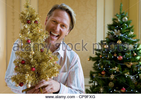 Mature man by Christmas tree with small ornamental tree, smiling, portrait - Stock Photo