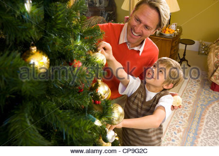 Father and son (9-11) decorating Christmas tree, elevated view - Stock Photo