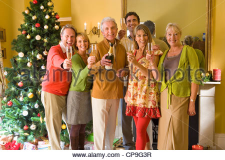 Family by Christmas tree proposing toast with champagne, smiling, portrait - Stock Photo