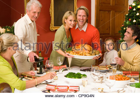 Family having Christmas dinner, portrait of couple with turkey - Stock Photo