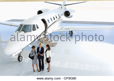 Businesswomen by aeroplane on runway, elevated view - Stock Photo