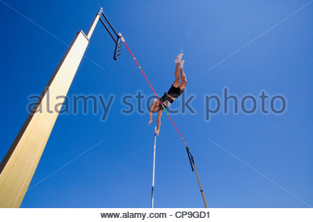 Pole vault athlete going over bar, low angle view - Stock Photo