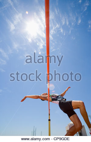 Young male athlete jumping over bar, low angle view (lens flare) - Stock Photo