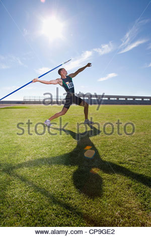 Male athlete preparing to throw javelin, low angle view (lens flare) - Stock Photo