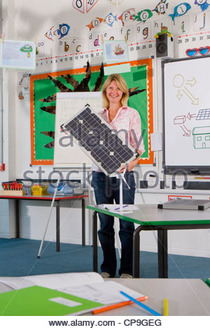 Smiling teacher holding solar panel in school classroom - Stock Photo