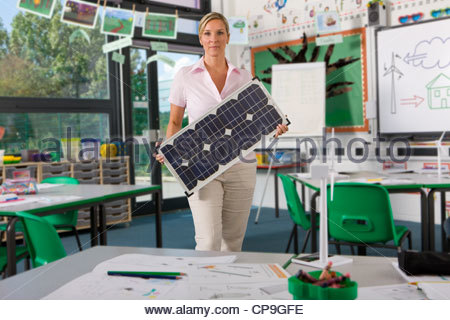 Serious teacher holding solar panel in school classroom - Stock Photo