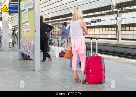 The German Railway in Berlin - Spandau.  A blonde young woman waiting on the platform for a train. interior of a - Stock Photo