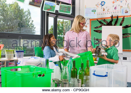 Teacher and students sorting recyclables together in classroom - Stock Photo