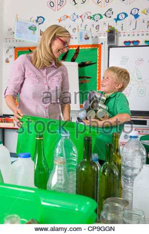 Teacher and student sorting recyclables together in classroom - Stock Photo