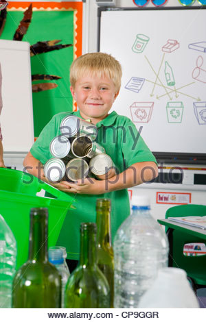 Smiling student holding recyclable tin cans in classroom - Stock Photo