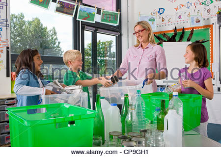 Teacher and students sorting recyclables in classroom - Stock Photo