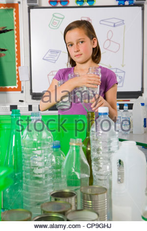 Serious student putting glass into recycling bin - Stock Photo