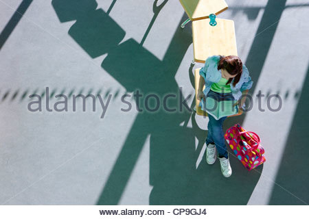 Student sitting on school desk studying textbook - Stock Photo