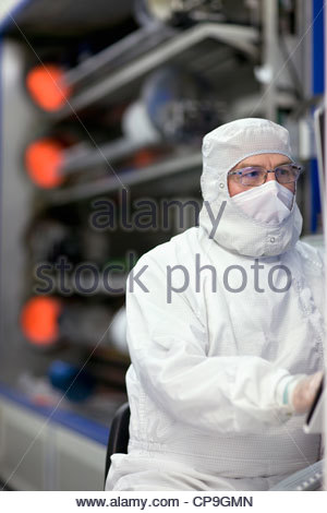 Engineer in clean suit working in silicon wafer manufacturing laboratory - Stock Photo