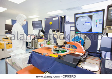 Engineer in clean suit working at computer in silicon wafer manufacturing laboratory - Stock Photo