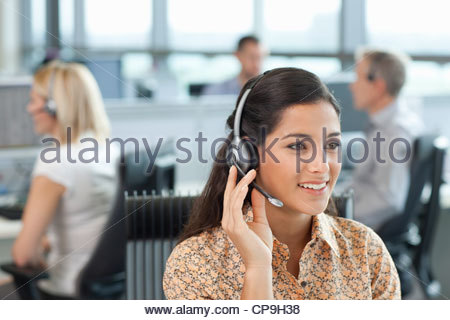 Business people wearing headsets in office - Stock Photo